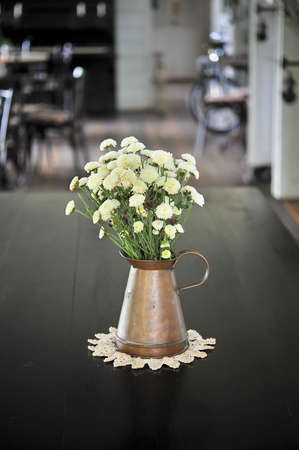 white flower in an antique metal jug on the black wooden tabletop photo