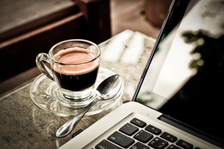 financial newspaper: Coffee cup and laptop for business.