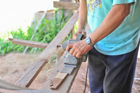 carpenter working with power tool while planing a piece of wood Stock Photo - 18565194