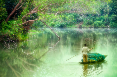 oarsman on nongchangkod River, Chiangrai, Thailand photo