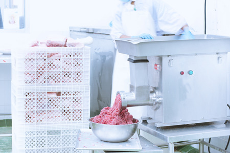 manufactory: worker mincing meat with mincer machine on manufactory Stock Photo