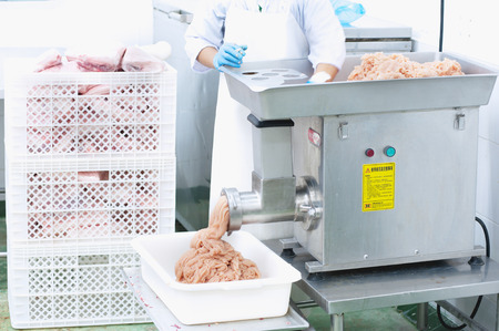 mincing: worker mincing meat with mincer machine on manufactory Stock Photo