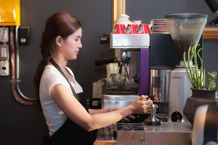 coffee mugs: Female bartender makes coffee using coffee machine. Stock Photo