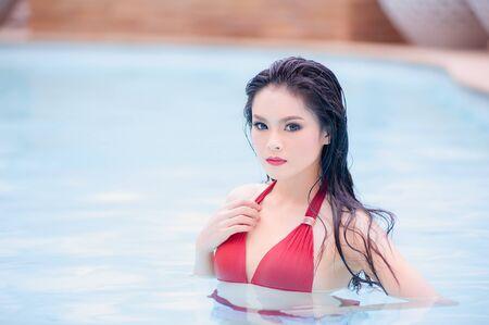 niñas en bikini: asia joven mujer sexy de pie en el agua en la piscina