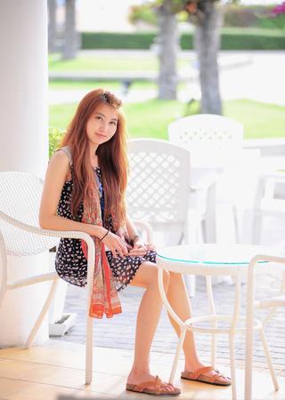 asia smile: Asia sonrisa mujer joven sentada en la silla blanca moderna, relajante