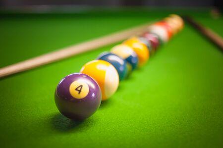 billiard ball: Billiard ball and cue on green table