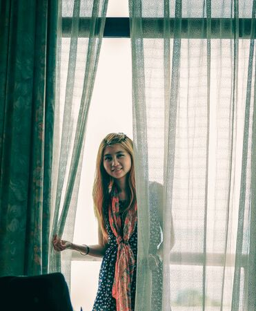 white curtain: Asia young girl holding white curtain near window Stock Photo