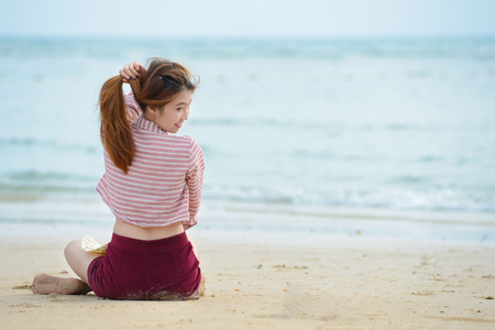 Asia young woman sitting on beach Stock Photo