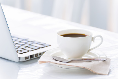 Coffee cup and laptop for business in coffee shop