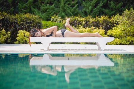 longue: bikini asia woman on sunbath longue by the pool