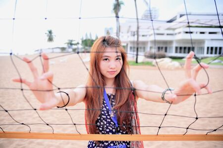 female volleyball: Asia young woman behind Volleyball net at the beach, sport concept Stock Photo