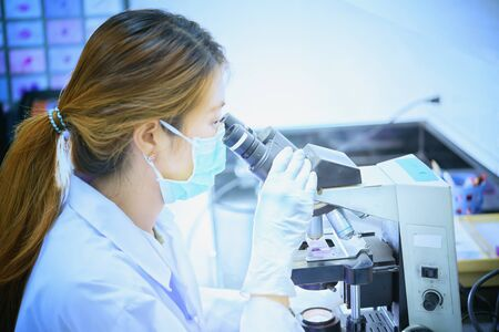 lab tech: scientist looking through a microscope in a laboratory hospital Stock Photo