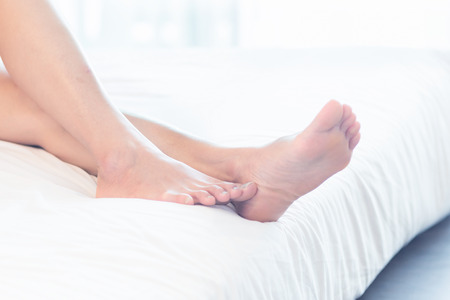 bed feet: Asia Young woman lying in bed in home with closeup of bare feet