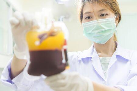 grupo de médicos: La bolsa de sangre en la mano Mujer del doctor asiático Foto de archivo