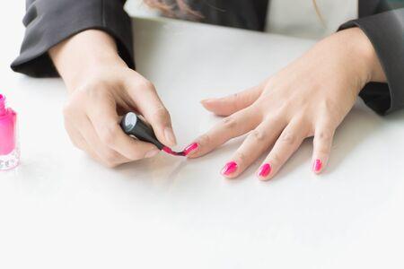 nails: Woman hand applying pink nail polish on white table Stock Photo