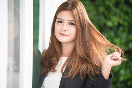 businesswoman suit: asia confident young businesswoman in suit holding hands on hair