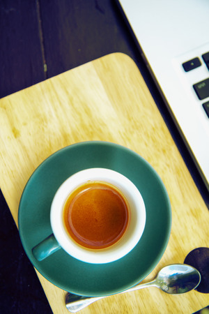 espesso: working time. hot coffee, espesso with laptop on wood teble. business concept