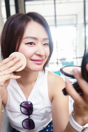 asian adults: make up woman holding powder puff