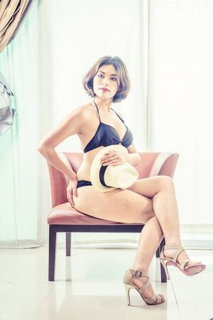 sexy pose: asia beautiful women in bikini sitting on chair at the room, vintage effect Stock Photo