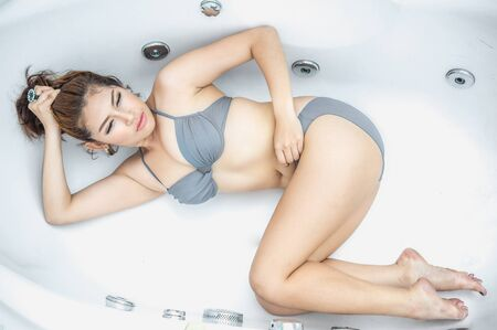 lying in bathtub: thai beautiful girl flop in the bath Stock Photo