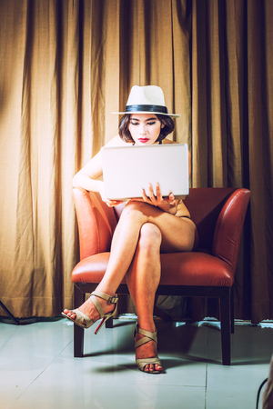 sexy girl sitting: asia beautiful bikini woman with laptop on chair at home, vintage style