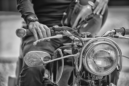 vintage power: Biker man sitting on his motorcycle, black and white style