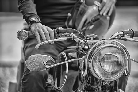 Biker man zittend op zijn motorfiets, zwart-wit stijl Stockfoto