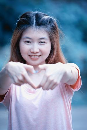 wahrnehmung: asia smiling cheerful young woman making heart sign with hands, Positive human emotion expression feeling life perception attitude body language, happy concept