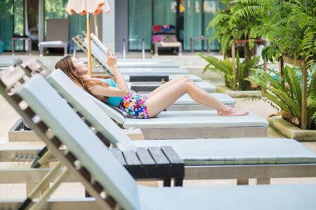 sitting pretty: Asia beautiful woman using a smart phone on lounger near swimming pool in hotel, krabi, Thailand