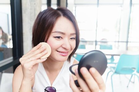 asian adult: make up woman holding powder puff
