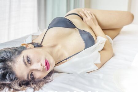 nude young woman: Young sexy woman in sexy black lingerie lying on bed