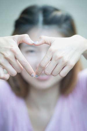 percepci�n: asia alegre sonriente joven mujer que hace signo de coraz�n con las manos, la expresi�n positiva emoci�n humana sintiendo percepci�n vida lenguaje corporal actitud, concepto feliz