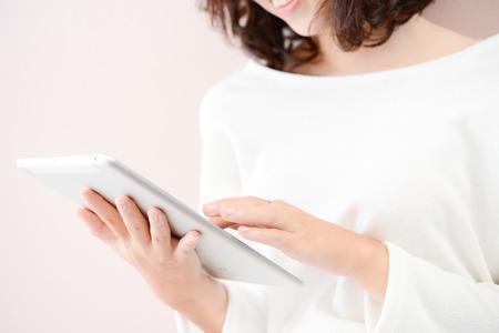 笑顔若いアジア女性を使用して、タブレット コンピューター、教育、技術の概念