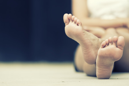 asia woman sitting on  floor. Feet close up. vintage effect