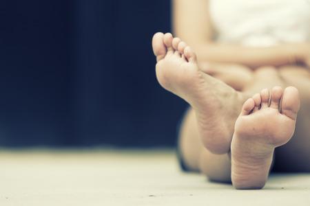 pies descalzos: asia mujer sentada en el piso. Pies de cerca. efecto de la vendimia