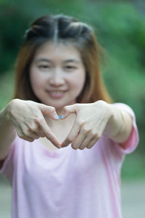 symbol women: asia smiling cheerful young woman making heart sign with hands, Positive human emotion expression feeling life perception attitude body language, happy concept