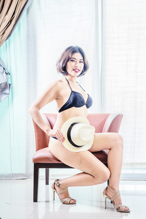 sexy girl sitting: asia beautiful women in bikini sitting on chair at the room, vintage effect Stock Photo