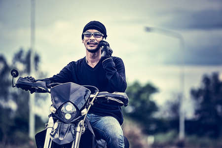 phone calls: portrait of asia handsome man biker call phone on the motorcycle, cross process effect Stock Photo