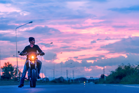 portrait of asia handsome man biker on the motorcycle in sunset, vintage effect Stock Photo
