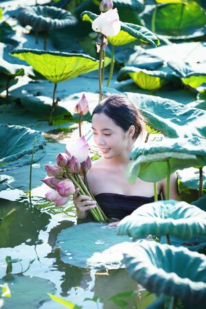lotus effect: amezing of beautiful young woman Farmer  collecting lotus in garden. thai lifestyle  people in local,Thailand, vintage filter effect Stock Photo