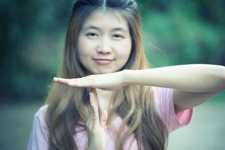 timeout: asia woman shows the hands stop timeout, hand symbol concept