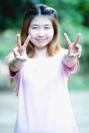 two fingers: asia young woman showing two fingers, positive or victory gesture Stock Photo