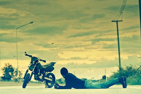 cross process: Biker relax lying with motorbike on country road in sunset, cross process effect Stock Photo