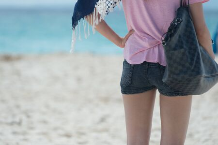 ass jeans: Young fashion woman in jeans shorts posing on the beach