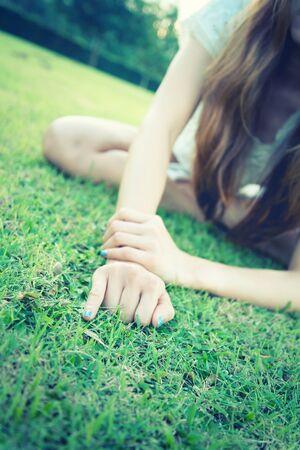 dedo meÑique: las mujeres de Asia se extiende con la mano mostrando el dedo meñique en la hierba verde en el parque Foto de archivo