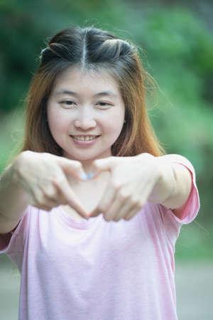 percepción: asia alegre sonriente joven mujer que hace signo de corazón con las manos, la expresión positiva emoción humana sintiendo percepción vida lenguaje corporal actitud, concepto feliz