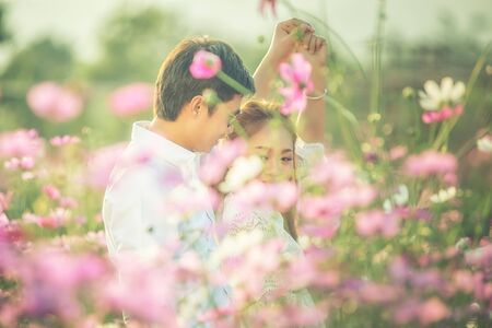 Asia young couple in love cuddling in lush garden and whirl in the dance