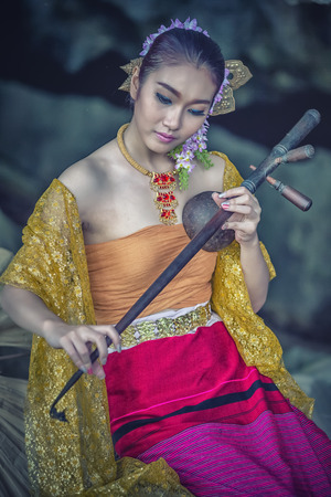 ancient sexy: asia women in ancient Thai dress playing Pinpia or Thai music Instrument Stock Photo