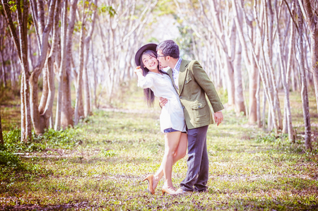 asai young romantic man and woman standing and hugging each other with tenderness in the field. Young love concept. Stock Photo