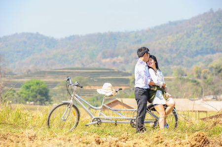 asai young romantic man and woman standing and hugging  with bike. Young love concept.